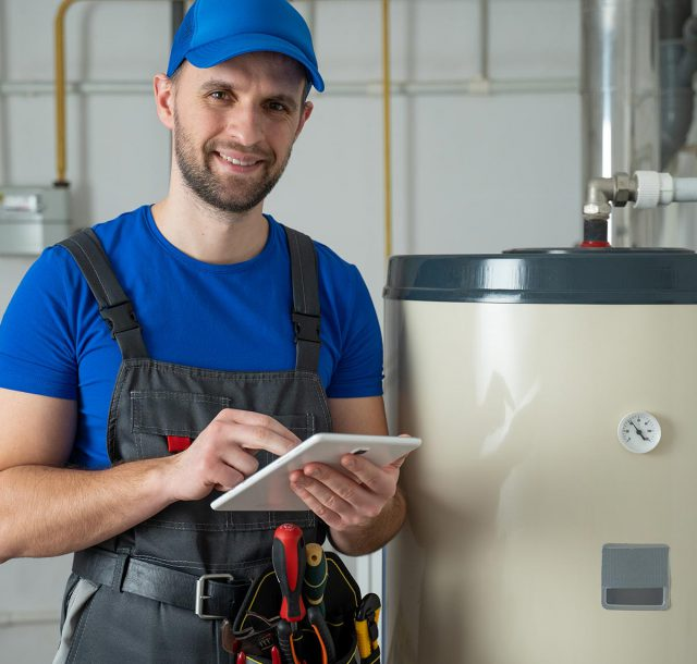 Technician servicing an hot-water heater. Man check equipment of the boiler-house - thermometer